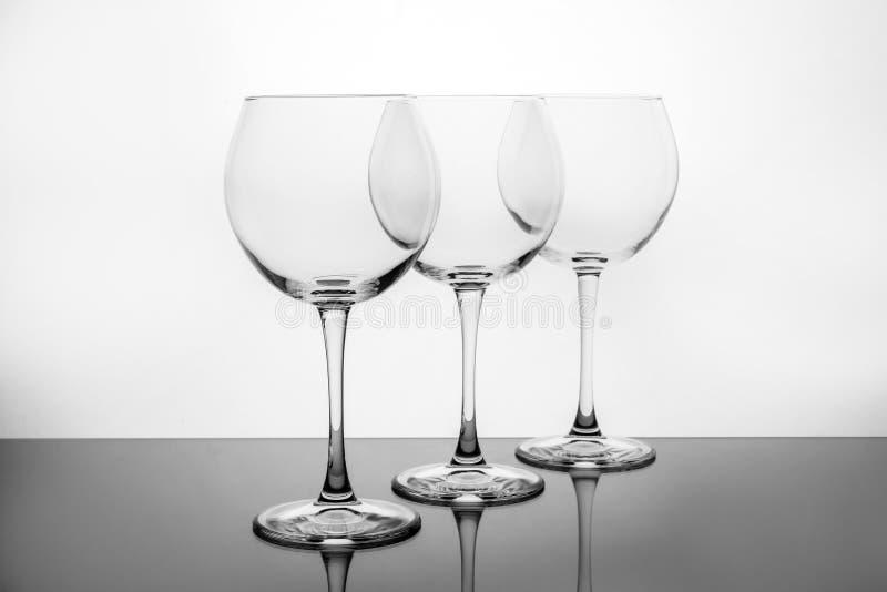 Rang?e des verres de vin vides sur le blanc images stock