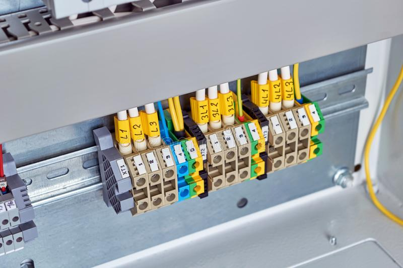 A range of electrical terminals fixed in an electrical Cabinet. Wires and cables with marking are connected to the terminals. Modern connection of the stock photo
