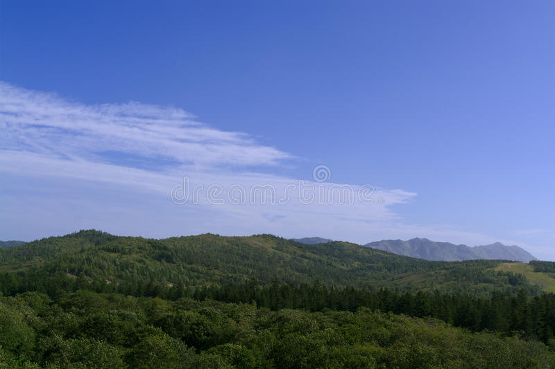 Range of low covered by forest Sakhalin mountains.  stock image