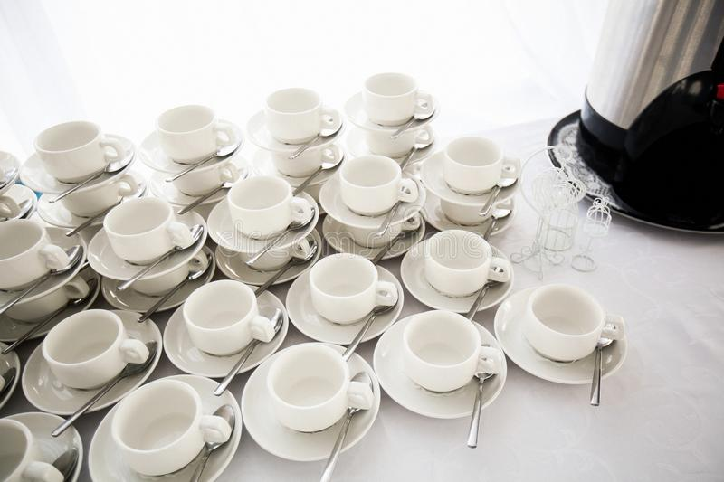 A range of traditional clean empty ceramic coffee cups on the table in the restaurant. Lots of white cups on saucers for serving stock photo
