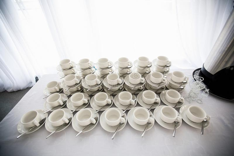 A range of traditional clean empty ceramic coffee cups on the table in the restaurant. Lots of white cups on saucers for serving stock image