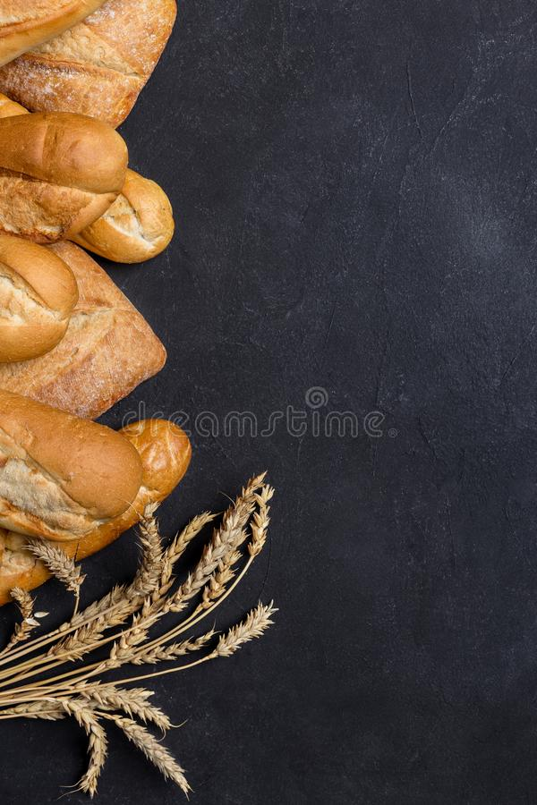 The range of types of fresh bread with grain. On dark rustic background. The range of types of fresh bread with grain. On dark background. Free space, top view stock photos