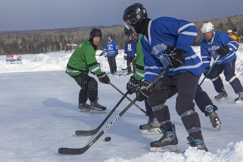Men`s teams compete in a Pond Hockey Festival in Rangeley. Rangeley, Maine/USA - February 4, 2017: Men`s teams compete on the ice at the 11th annual New England royalty free stock photo