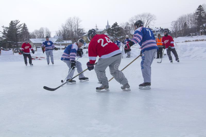 Men`s teams compete in a Pond Hockey Festival in Rangeley. Rangeley, Maine, USA - February 4, 2017: Men`s teams compete on the ice at the 11th annual New royalty free stock photography
