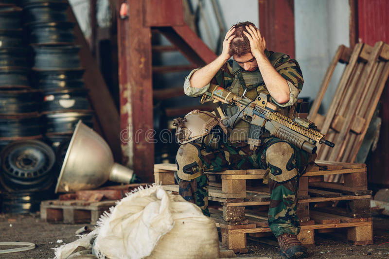 Ranger sitting with arms and hands holding her head stock image
