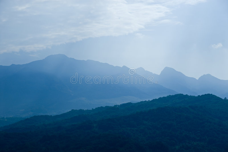Rango de montaña en niebla azul fotografía de archivo