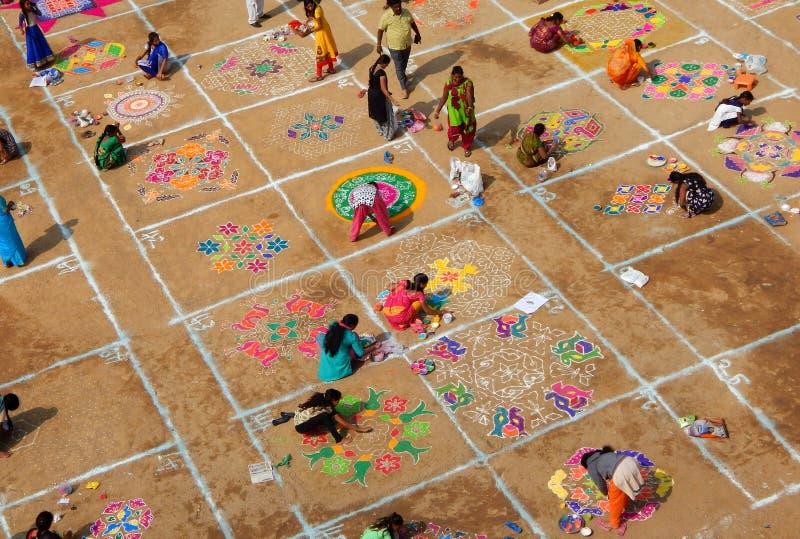 Rangoli indù di tiraggio della donna con le polveri colorate, fiori in festiva di makara o pongal di sankranti fotografie stock