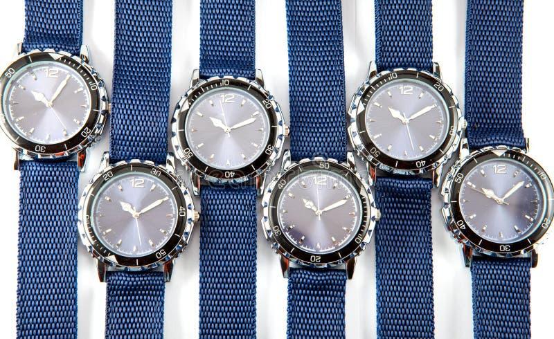 Rangordnar av en man klocka med blåttvisartavlan och slösar lies för en thong på en vitbakgrund arkivfoto
