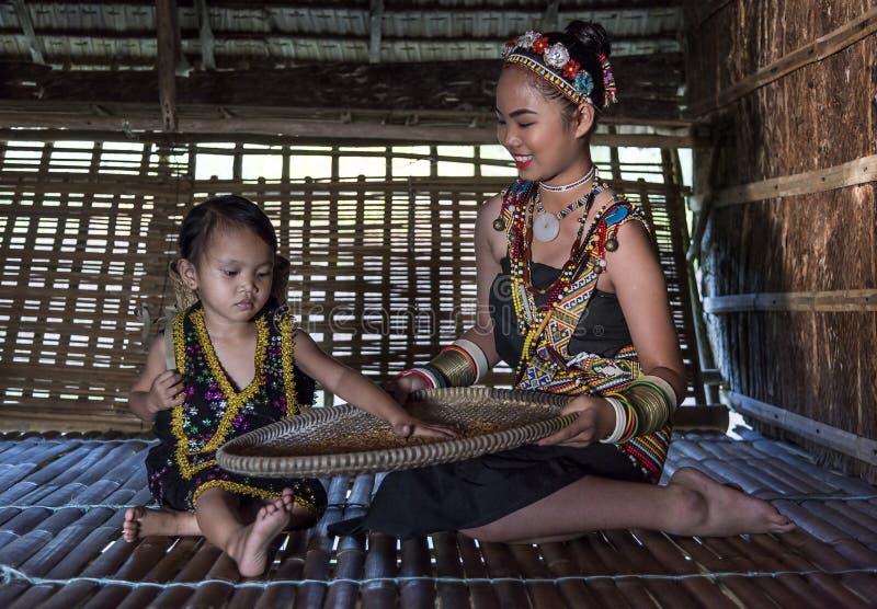 Rangus plemienna kobieta w jej tradycyjnym plemiennym kostiumowym działaniu w jej domu w Kudat, Malezja obrazy stock