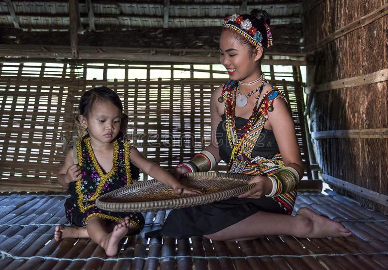 Rangus tribal Woman in her traditional tribal costume working in her house in Kudat, Malaysia stock images