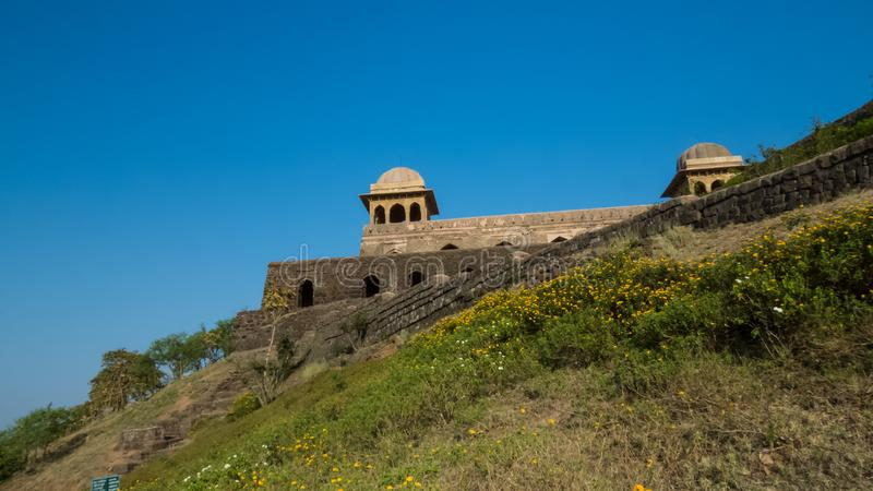 Rani Rupmati Palace on the Hill Top-Mandu-India. The Palace of Rani Rupmati on the Hill Top at Mandu-India. Yellow flowers of marigold on the slope of hill and stock photography