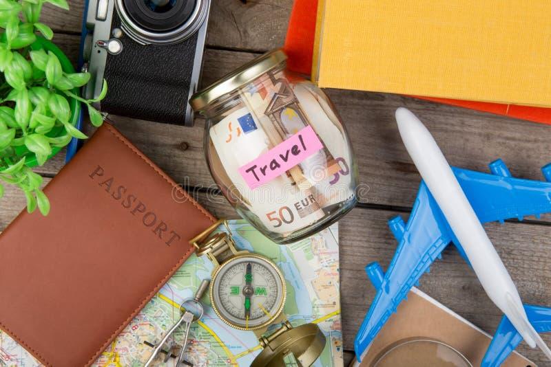 Ranja com dinheiro para um curso, mapas, passaporte, e o outro material para a aventura na tabela fotos de stock