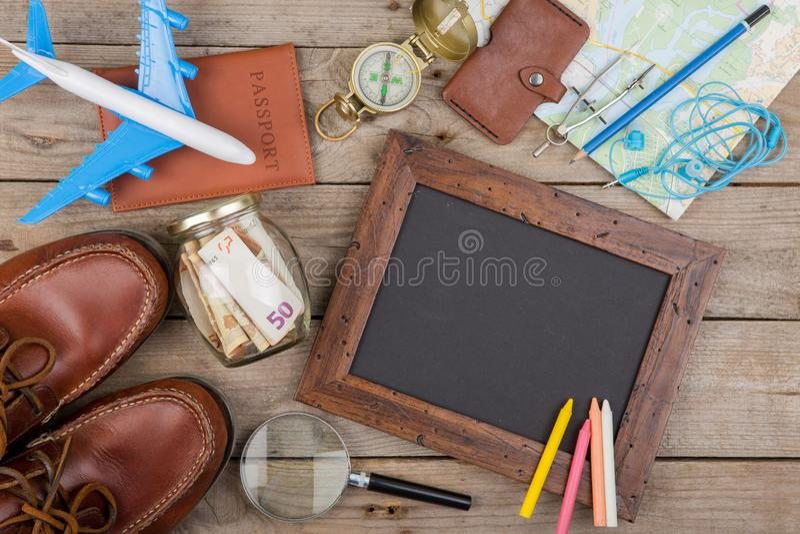 Ranja com dinheiro para um curso, mapas, passaporte, e o outro material para a aventura na tabela fotografia de stock