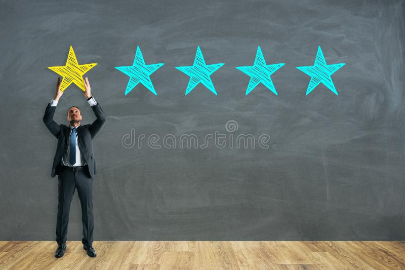 Ranking and appraisal concept. Young businessman on chalkboard background with five star rating. Ranking and appraisal concept stock photography