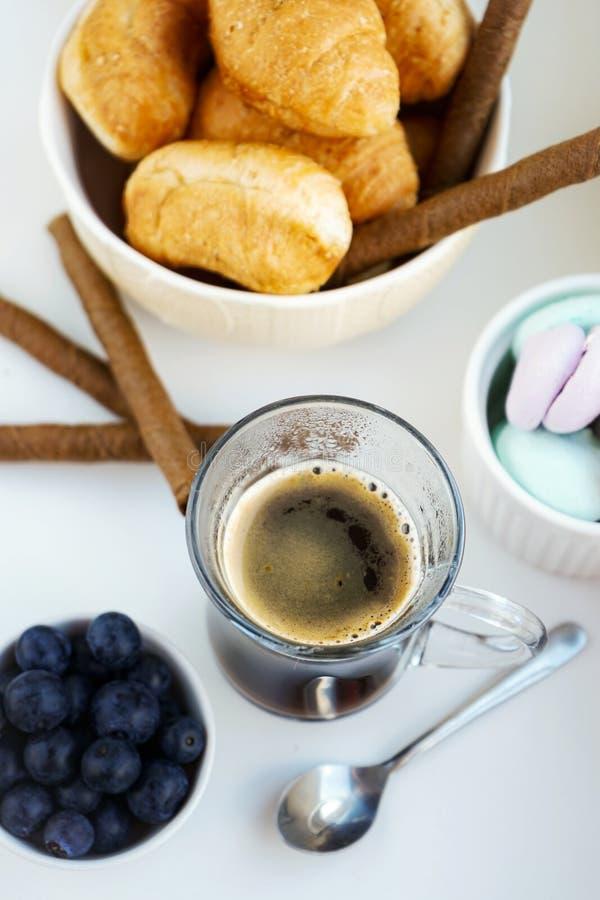 ranku Śniadaniowy filiżanka kawy, croissants, barwione słodkie bezy, czarne jagody w glinianym białym szkle zdjęcia stock