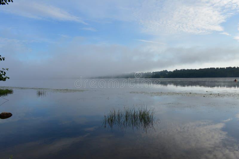 Ranku rzeczny rybak na łodzi, niebieskie niebo chmury odbijał w gładkim fotografia royalty free