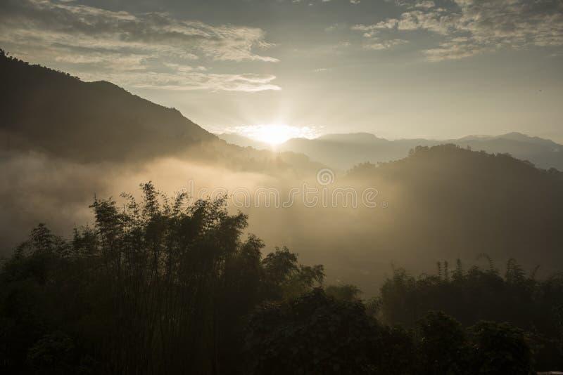Ranku słońca promienie przez mgły nad halnymi skłonami obrazy stock