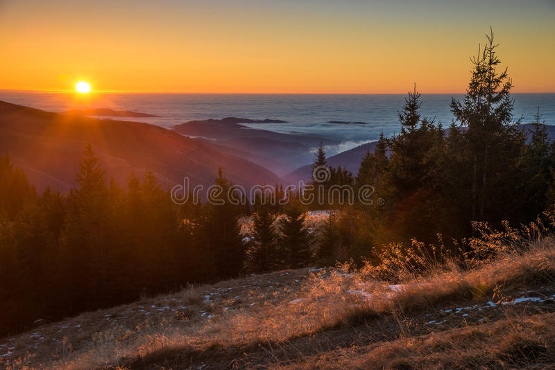 Ranku słońce penetruje mgłę i iluminuje góry i chmury obraz stock