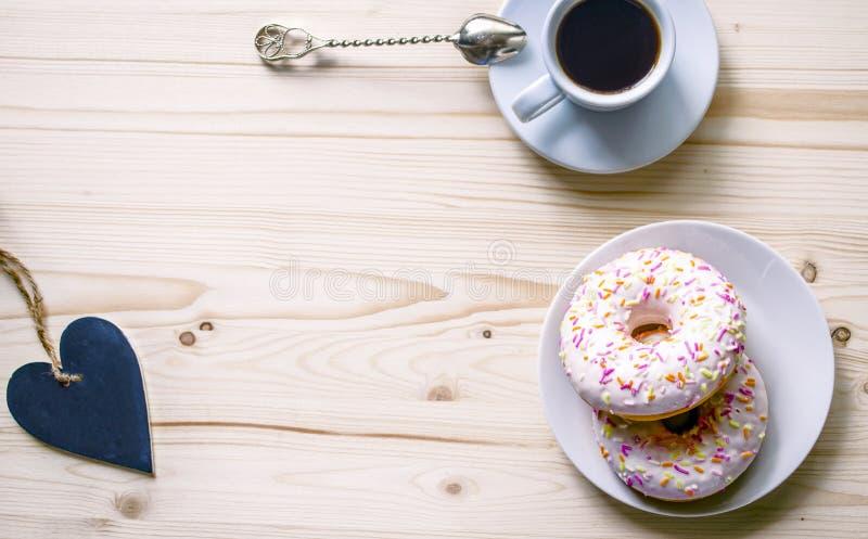 Ranku skład z kawą i donuts na drewnianym stole Przestrzeń dla prezentaci pracy lub tekst fotografia stock