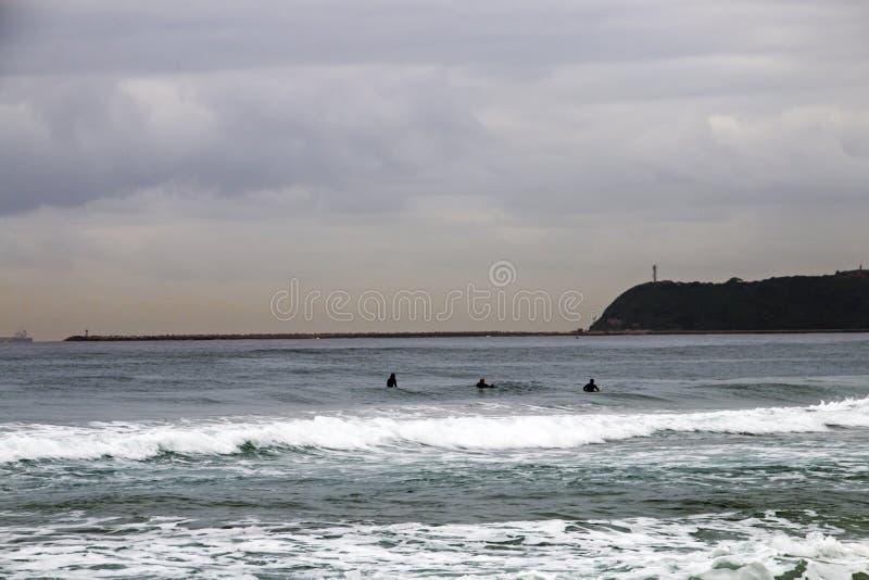 Ranku widok surfingowowie i plaża Przeciw blefowi obraz royalty free