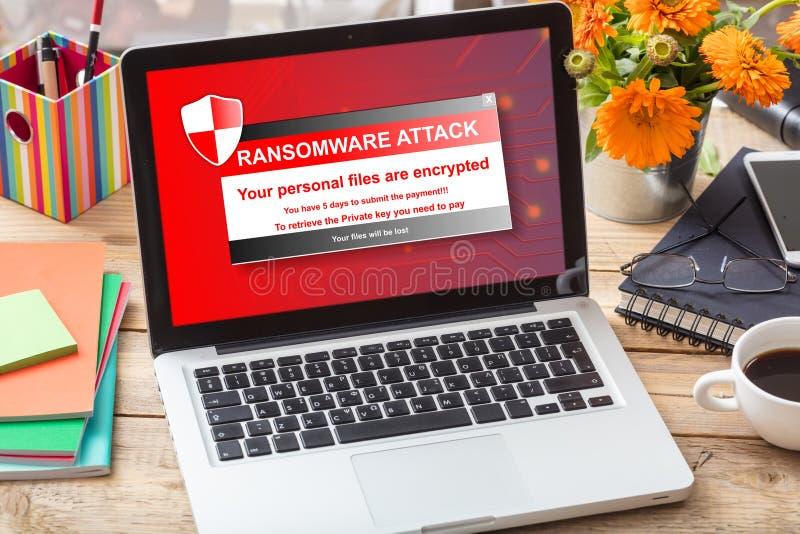 Ransomware在一个膝上型计算机屏幕上的攻击消息在办公桌上 免版税库存照片