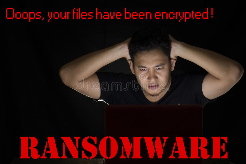 Ransomware Computer Virus. Young man shocked in front of his laptop in the dark to see his files on his computer have been encrypted by ransomware virus stock images