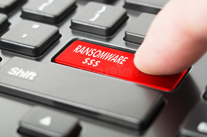 Ransomware written on keyboard button. With finger pressing on it royalty free stock photo