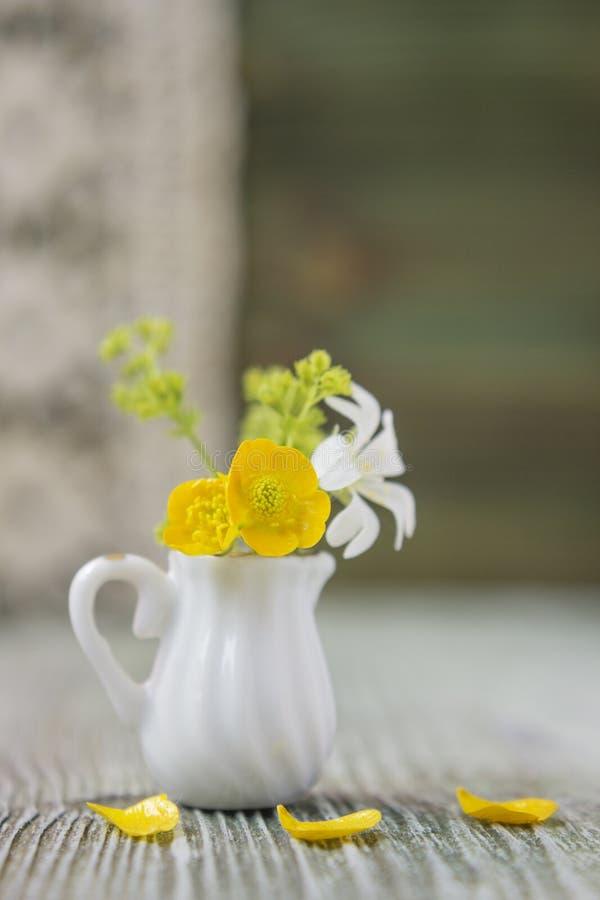 Ranunculus bouquet in miniature, diminutive jug. Macro close-up photo with soft focus, bouquet of buttercup flowers. Rustic backgr stock image
