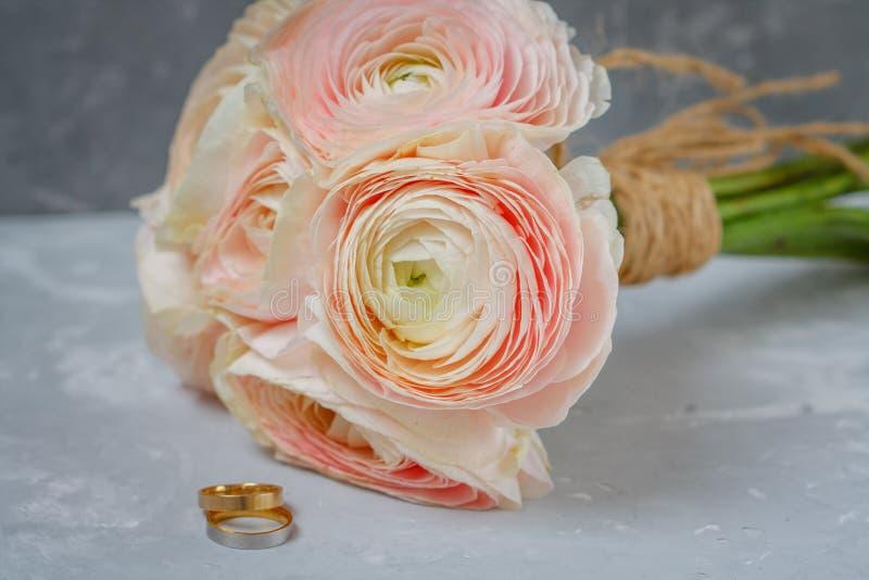 Ranunculusblumenstrauß nahe bei den Eheringen stockfotos