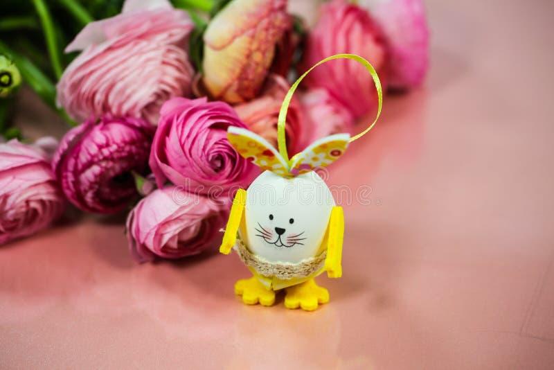 Ranunkeln en el rosa, macro, primavera, asiaticus del ranúnculo de las flores con el huevo de Pascua fotos de archivo