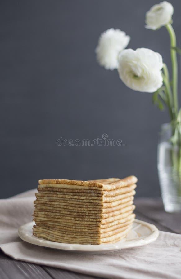 Ranunkulyus-Butterblumeblumenstrauß Hintergrund der goldenen russischen Serviette der Pfannkuchen grauen dunkler lizenzfreies stockfoto