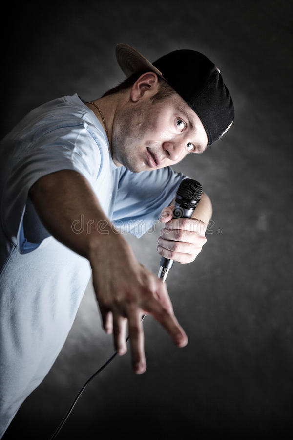 Rap singer man with microphone cool hand gesture. Rapper attitude rap singer hip Hop Dancer performing. Young man with microphone singing hand cool gesture black royalty free stock image