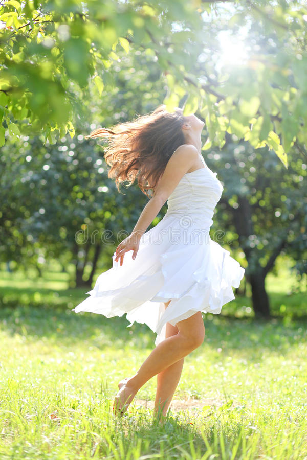 Rapariga adorável na roupa branca que aprecia fotos de stock royalty free