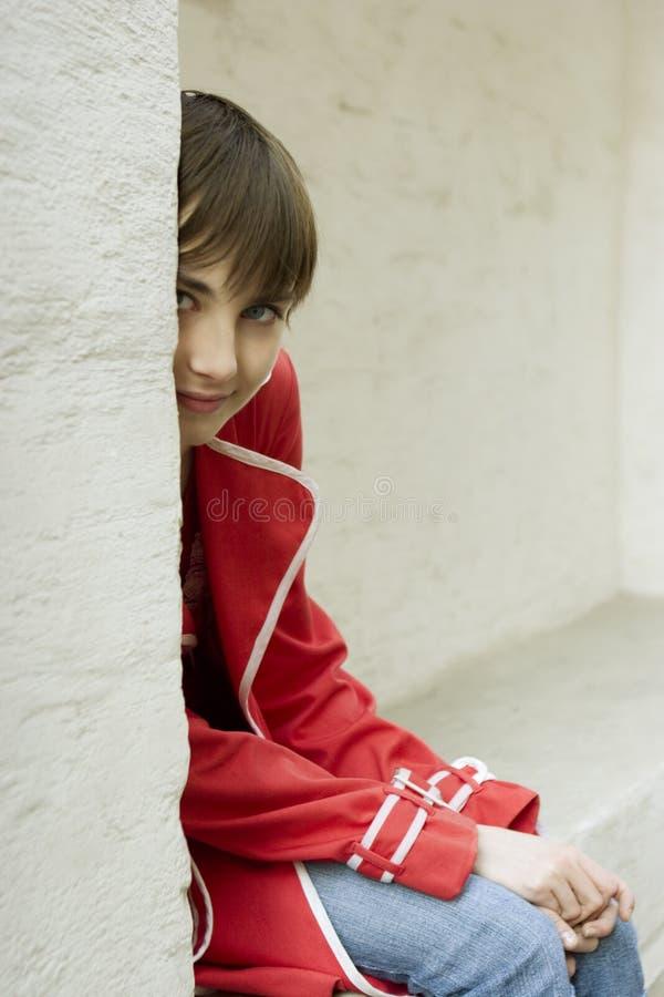 A rapariga atrativa está sentando-se perto da parede fotografia de stock