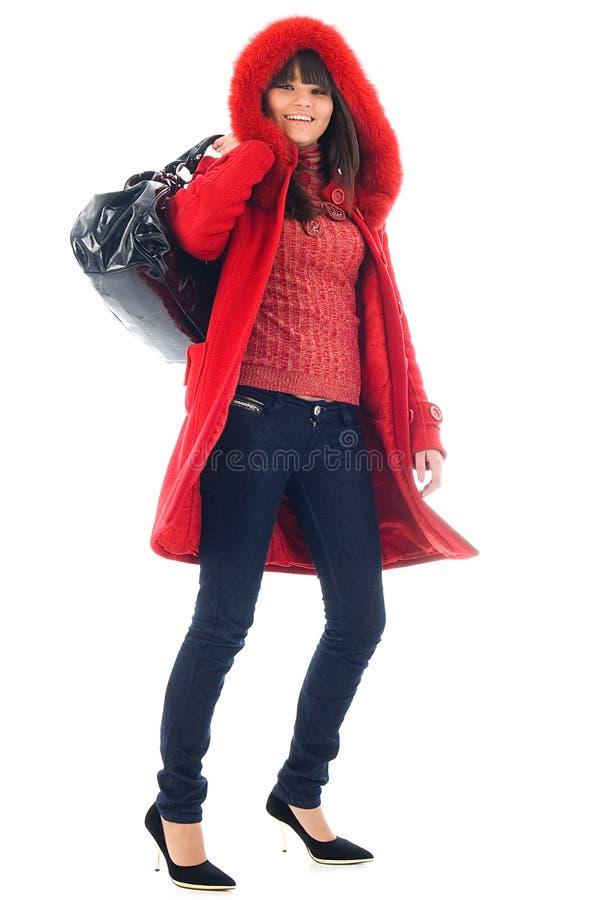 A rapariga bonita em um revestimento vermelho imagens de stock royalty free