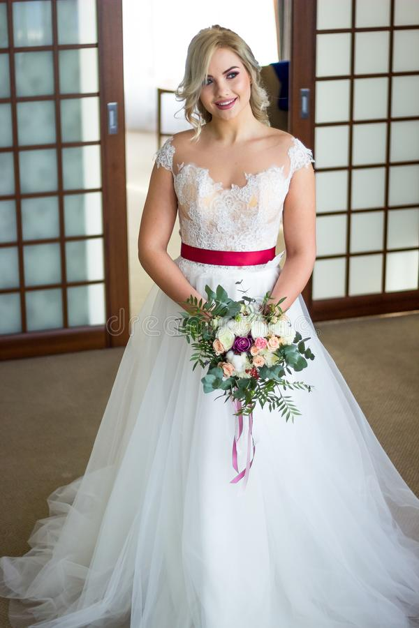 Rapariga bonita Mulher loura com a cauda longa luxuoso do cabelo Manhã do boudoir da noiva Tomando o ramalhete do casamento em su imagem de stock royalty free