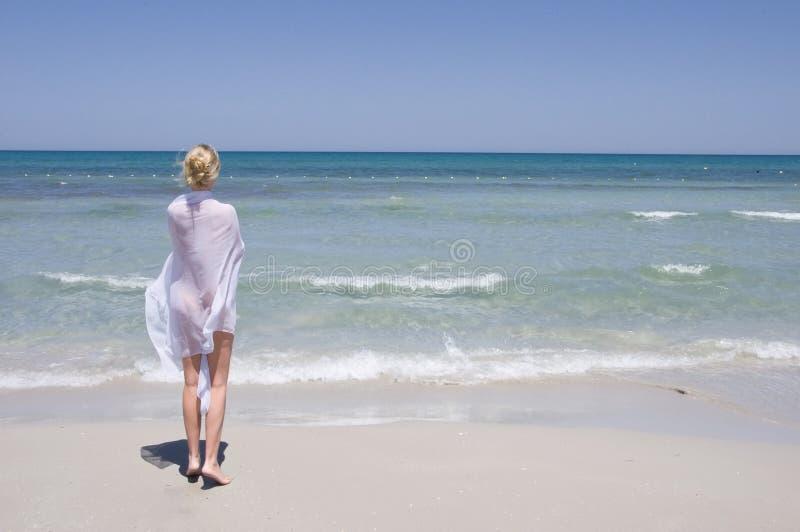 Rapariga bonita no passeio branco na praia fotografia de stock royalty free