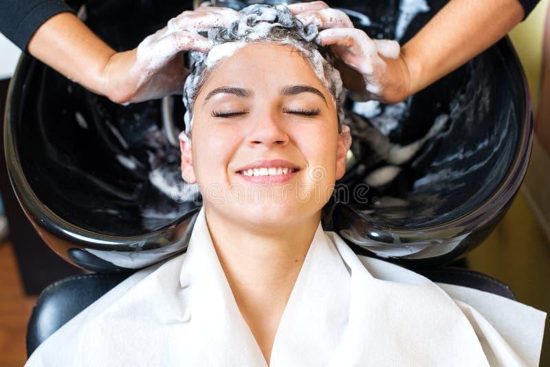 Rapariga bonita que aprecia o cabelo que lava no salão de beleza do hairdressing fotos de stock