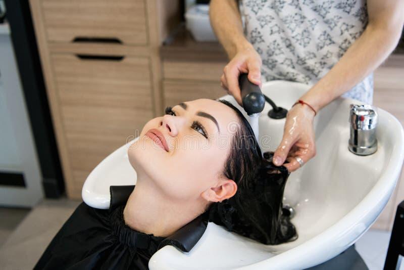 Rapariga bonita que aprecia o cabelo que lava no salão de beleza do hairdressing foto de stock