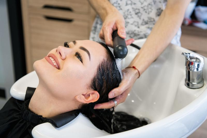 Rapariga bonita que aprecia o cabelo que lava no salão de beleza do hairdressing foto de stock royalty free