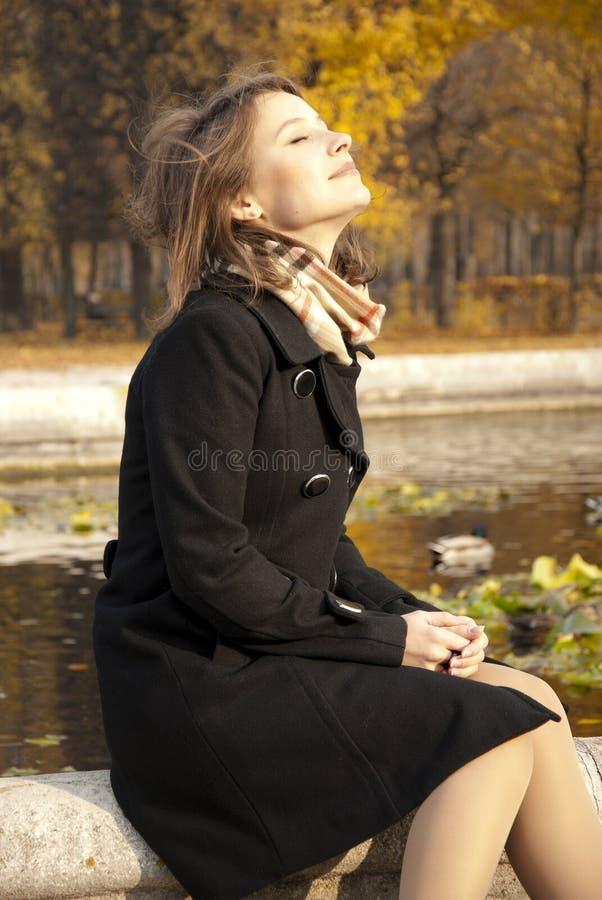 Rapariga bonita que aprecia o sol do outono fotografia de stock