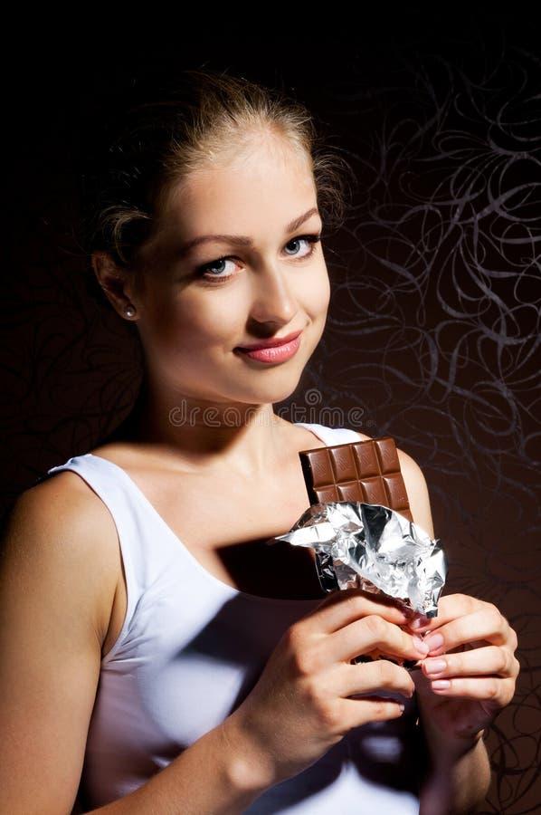 Rapariga bonita que come o chocolate imagem de stock royalty free