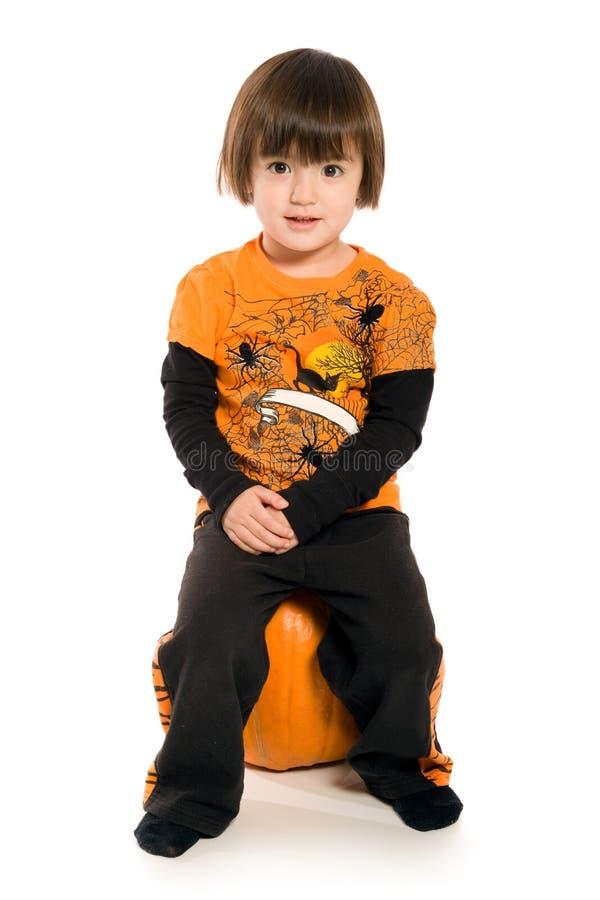 Rapariga bonita que senta-se na abóbora fotografia de stock royalty free