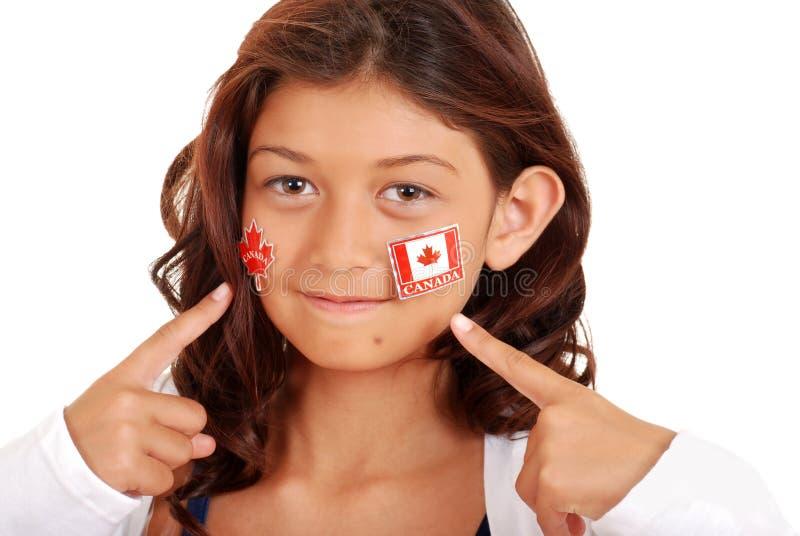 Rapariga com etiquetas do dia de Canadá na face fotos de stock