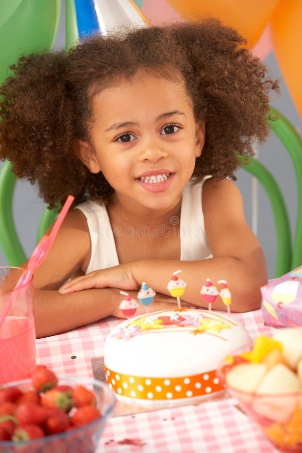 Rapariga com o bolo de aniversário no partido fotografia de stock royalty free