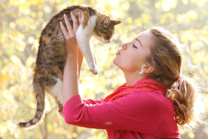 Rapariga com o gato no fundo natural fotos de stock royalty free