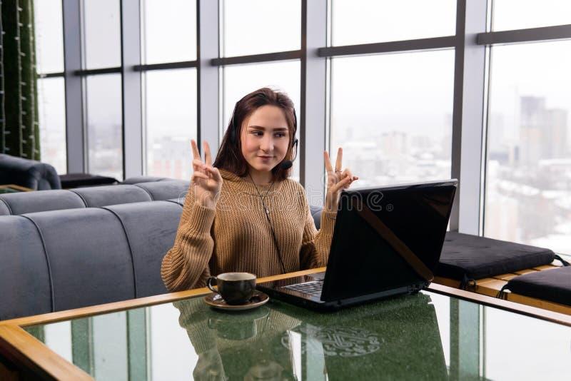Rapariga conduz uma transmissão online da cafeteria e faz um gesto de vitória fotografia de stock royalty free