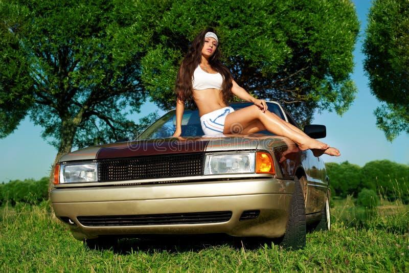Rapariga da beleza que lava um carro no por do sol do verão imagem de stock