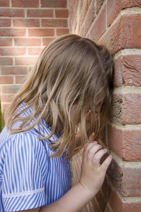 Rapariga de encontro a uma parede de tijolo foto de stock
