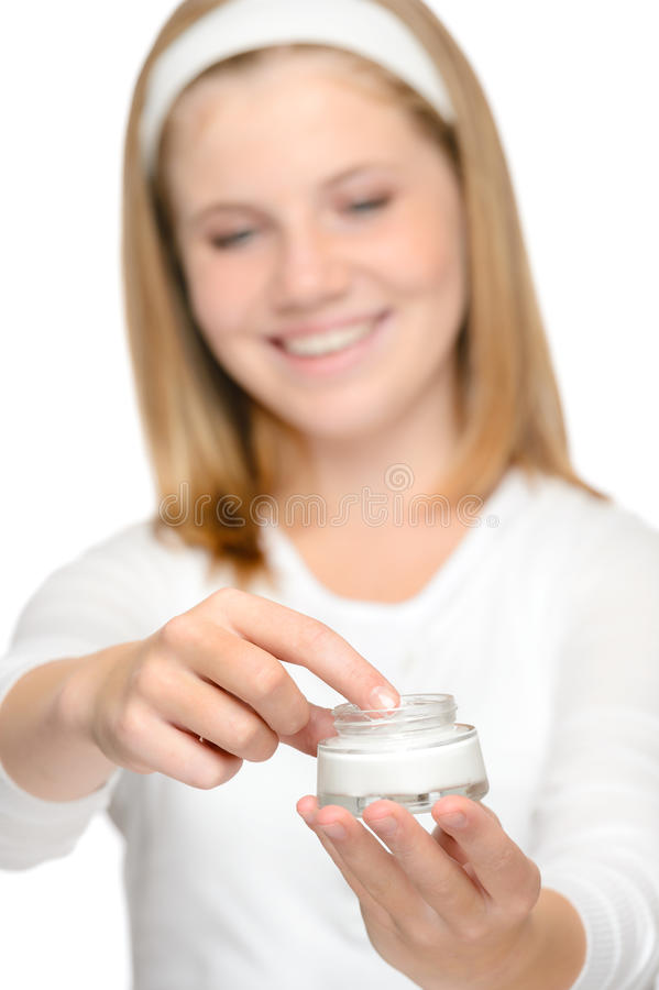 Rapariga de sorriso que aplica a cara de creme do creme hidratante fotografia de stock